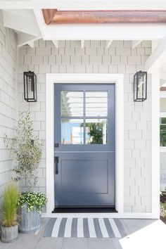 Gray beach home features a blue front door with windows styled with a striped do.Gray beach home features a blue front door with windows styled with a striped doormat, galvanized planters and gray shingles illuminated Exterior Gris, Exterior Doors, Exterior Design, Dutch Door Exterior, Stucco Exterior, Entry Doors, Entrance, Exterior Signage, Exterior Stairs