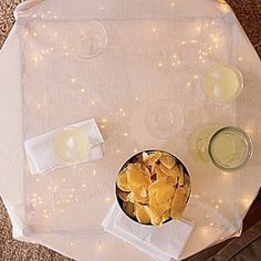 Under a glass table.  Put string lights under a glass table and use a sheer cloth.
