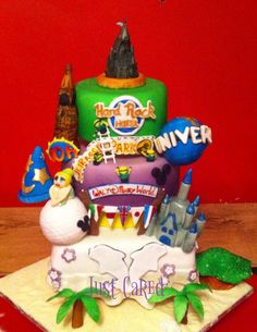 Orlando themed cake featuring Disneys Magic Kingdom, Epcot, Hollywood Studios, and Animal Kingdom, Universal Studios and Islands of Adventure, Hard Rock hotel and the famous guitar fountain, Minions, Dolphins, Tinkerbell, 5 of Epcots country flags, palm trees and a wedding dress tier to represent a wedding on Cocoa beach Fl.   This cake took a week from flour to finish!