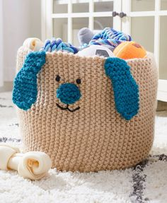 Free Knitting Pattern for Easy Puppy Basket - Perfect basket for storing dog toys or a dog loving child's toys. Knit in garter stitch with a double strand of yarn for sturdiness. The face is embroidered with ears and nose knit separately and sewn in place. Designed by Heather Lodinksy for Red Heart.