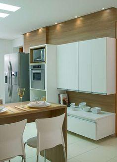 A cozinha americana de 7m², projetada pela arquiteta Cinthia Garcia e a designer Andréia Karalkovas, conta com cores neutras e faixa de pastilhas metalizadas para contrastar com a sala. Apresenta coluna para o forno e micro-ondas, além de bancada com cook top. Informações: (11) 4224-2000 Foto: Marina Palácio