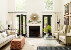 Beautiful living room with tall second story windows over black French doors dressed in floor length cotton drapes flanking simple fireplace with gold sunburst mirror over mantle. Description from decorpad.com. I searched for this on bing.com/images