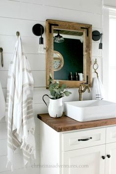 Vessel sink with aged brass faucets, shiplap, butcher block, wood framed mirror, black sconces, and turkish towels on vintage hooks