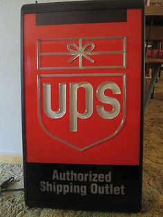 "UNITED PARCEL SERVICE LIGHTED SIGN     •1995 DOUBLE-SIDED UNITED PARCEL SERVICE LIGHTED SIGN (UPS)   •RAISED LOGO ON ONE SIDE FOR NEON TYPE EFFECT, OTHER SIDE GRAPHICS ARE FLAT    •APPROX. 15 1/4"" x 27 1/2""   •LOOKS GREAT WHEN LIT!"