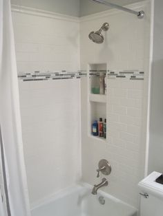 tub/shower enclosure with accent band. white subway tiles