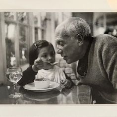 Paloma Picasso having her father taste a crême caramel at La Galloise, Vallauris…