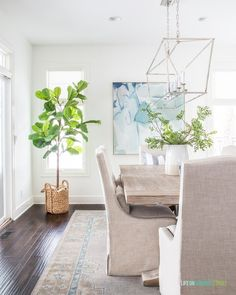 The best faux fiddle leaf fig tree in a dining room with faux greenery, linen dining chairs, a vintage style rug, and abstract art. Blue Gray Paint Colors, Gray Color, Life On Virginia Street, Backyard Renovations, Reclaimed Wood Dining Table, Wood Table, Fiddle Leaf Fig Tree, Lounge Areas, Coastal Decor