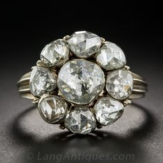 Georgian Style Rose Cut Diamond Cluster Ring. From mid-twentieth century Holland, a sparkling Retrospective Georgian style cluster ring featuring nine closely huddled rose-cut diamonds, each glittering from within as many foil-backed closed settings. The 5/8 inch round crown is supported by neoclassical scroll motif shoulders. The center measures just under a carat, and the eight smaller rose-cut diamonds bring the total diamond weight to approximately 4.40 carats