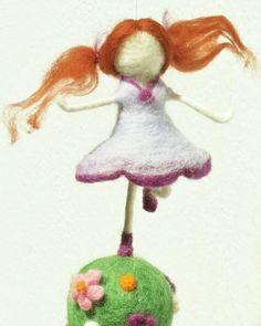 Menina feltrada correndo sobre uma bola com flores