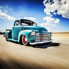 Chev Chevy Chevrolet Advanced Design pickup truck in a sweet aqua blue over read wheels sporting stainless trim rings and baby moon hub caps all flying down the freeway for a really great motion shot.