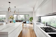 Flat white kitchen timber floors windows overlooking pool#flat #floors #kitchen #overlooking #pool #timber #white #windows