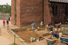 Archaeologists actively dig the site of the 1607 James Fort while a crowd looks on