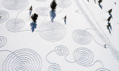 Artist Simon Beck's immense snow crop circles are made entirely by foot, and are created when Beck walks around the terrain in briquette snow shoes!