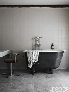 A vintage tub with fittings by Mora Armatur in a bathroom; the floor is tiled with Carrara marble.