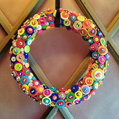 Round headed pins are used to hold the buttons on a Styrofoam wreath.