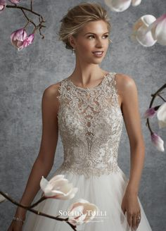 Sophia Tolli Y21745 Aquila - Sleeveless misty tulle and lace motif ball gown with high illusion lace neckline, plunging sweetheart bodice adorned with hand-beaded lace appliqué, beaded illusion lace back features zipper trimmed with diamante buttons, asymmetrically tiered tulle skirt with chapel length train. Also available with a 3 inch raised back neckline as Y21745HB.