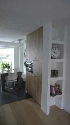 Om de kastenwand meer af te scheiden van de woonruimte is er voor gekozen om een open kast te creëren die volledig van vloer tot plafond loopt. Op deze wijze kijk je niet tegen een zijwand van de hoge kast maar wordt hij meer in de ruimte geïntegreerd. Overigens zijn ook de hoge kasten volledig tot aan het plafond gemaakt zodat het geheel een rustige uitstraling geeft. Het keukenbureau Harderwijk