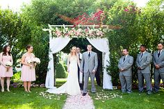 Bride and Groom Under Arbor with Pink Rose Petals