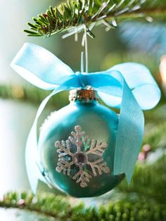 """""""Snowflake Gem Ornament: Give a simple ornament an elegant update with a layering of glittery snowflakes. Glue a snowflake punched from colored vellum to the ornament. Top the snowflake with a white snowflake sticker and add a silver gem to the middle for extra sparkle. A ribbon bow on top finishes the look."""""""