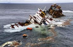 Half of a cargo ship that ran aground on a New Zealand reef three months ago began sinking into the ocean Tuesday, and debris and some oil were drifting from the wreck.