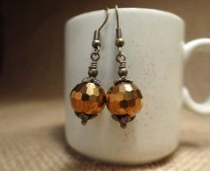 Brass Autumn earrings. Fall Brass and Faceted brass colored faceted glass earrings. These beautiful earrings reflect the color and tone of Fall. Gorgeous brass colored faceted glass beads are capped on both ends by antiqued brass floral bead caps and tiny brass beads. These earrings dangle from antiqued brass beaded fish hook style ear wires and are nickel free. Ready to ship. Thanks for visiting! See so much more at my shop. https://www.etsy.com/shop/bulletsbeadsbaubles. Check out my…