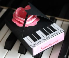 """A special gift for the music lover. This piano sleeve fits perfectly around a box of sweetheart candy hearts and is finished off with a beautiful rose and the sentiment """"You're music to my ears."""""""