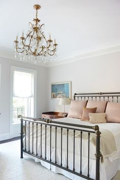 Feminine bedroom with a vintage metals headboard and a chandelier