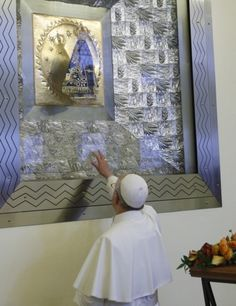 Pope Francis touches the glass protecting the statue of Our Lady of Aparecida before celebrating Mass at Brazil's Basilica of the National Shrine of Our Lady of Aparecida July 24. During his visit, the pope entrusted World Youth Day to Mary's maternal protection, but also challenged parents, priests and other adult Catholics to give the young people things that the world, with all its wealth, cannot: faith and values. (CNS photo/Paul Haring)