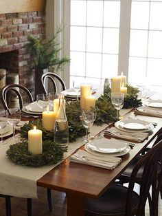 design dump: holiday tablescapes. Wreaths as candleholders, on a (burlap?) runner...