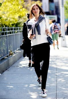 Gray knit sweater knotted around shoulders, white button-down blouse, black cropped trousers, and metallic sneakers