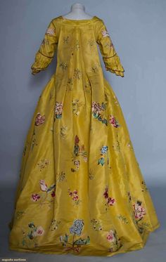 Back view, robe à la Francaise, 1765. Goldenrod silk faille, tour de force embroidered exotic florals worked in various stitches and incorporating silk fabric appliques in larger blossoms, also small bird and insect embroidery.