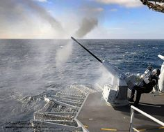 A sailor onboard HMS Ocean fires a 20mm Gambo Cannon during an exercise at sea.