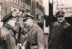 """Reichsführer SS Heinrich Himmler speaks with Anton Mussert, the leader of the Dutch Nazis, during a visit of the former to the Netherlands. Dr. Seyss-Inquart, Reichskommissar in Holland, is the tall man obscured by Himmler. To the right is SS-Obergruppenführer Karl Demelhuber. Himmler had high """"Aryan"""" hopes for the Dutch, whom he considered closely related to the Germans."""