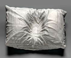by Sebastian Martorana.    Marble sculpture of the impression made in the pillow of his late father in-law after lifting him up from his death bed. 2008.
