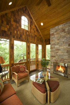 """This porch is similar to a covered patio, with """"windows"""" and a fireplace. The porch is reached by a way of a long flight of stairs."""