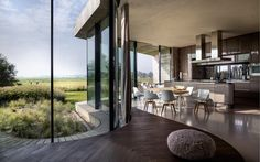 Kitchen and eating area takes advantage of a curving glass wall to look out on a gorgeous countryside in North Holland, Netherlands. - reddit