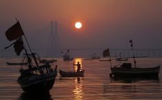 A fisherman anchors his boat in the low tide sand as the sun sets in Mumbai.