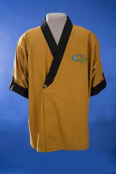 """James Kyaw Gold Sushi Chef Jacket, c. 1986 - Asian immigrants and families coming to the U.S. have often found work in th efood services industry and built successful small businesses. The jacket was worn by James Kyaw a sushi chef for Advanced Fresh Concepts Corporation (AFC). The design is based on the Japanese happi coat, a straight sleeve coat. It is gold with a navy trim and fastens with one button in the front. The AFC logo, """"Southern Tsunami,"""" is embroidered on the left breast panel."""