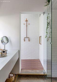 Banheiro com revestimento de subway tiles, chuveiro de cobre e deck de madeira.: