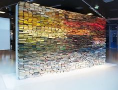 The working title of The Wall of Books by dutch artist ANOUK KRUITHOF is 'Enclosed content chatting away in the colour invisibility' and was first built in 2009. On every exhibition the book-wall gets installed in a different order and thus changes its appearance and becomes a new piece of art every time it is set up.