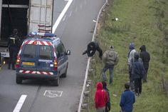 """A migrant jumps over the highway barrier as French gendarmes inspect a truck on the highway close to the """"New Jungle"""" make-shift camp in Calais, northern France, October 15, 2015. More than 3,500 people, migrants and refugees are camped in Calais, fleeing war and poverty in the Middle East, Africa and Asia and now living in the jungle. Most of them are hoping to make the crossing to England. REUTERS/Philippe Wojazer"""