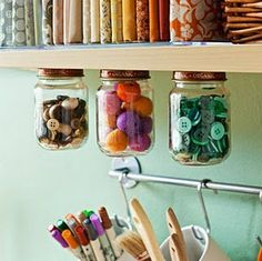 In my Granpa's basement he'd nailed the lids to babyfood jars to the floor joists over his work bench, creating storeage for tacks, nails, screws and what have you.  Nice idea for buttons and sewing/craft items, too!