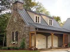 Stonework and colonial 6/6 windows, shed roof dormers with siding following the roof slope (classic colonial), arched carriage-house garage doors, square trellis at ends shed roof ends, window planter box, faux fireplace (it's the round window in the gable that gave it away, also that it's a garage), standing-seam metal roof, round metal downspouts, real working shutters.