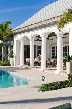 Stunning indoor-outdoor loggia with columns framing the view of the pool.