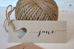 I love the idea of a very simple and nice cardstock with a pretty font for the name & table number with a heart-shaped hole and ribbon.  Simple + Inexpensive.  #diywedding Wedding place cards/name tags/favour bag tags by LaPommeEtLaPipe, $0.50