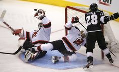 New Jersey Devils goalie Martin Brodeur makes a save during the second period during Game 3 of the NHL Stanley Cup hockey finals in Los Angeles as LA's Jerret Stoll #28 storms the New Jersey Net