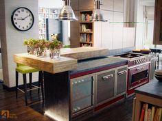 Love the contrast between an industrial tough kitchen with the delicate wooden counter and floral arrangements.
