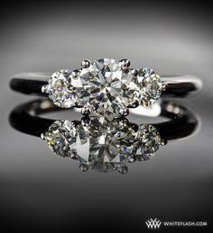 Three exquisitely cut diamonds comprise a ring that glows with resplendent brilliance.