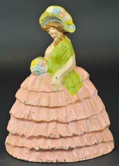 "COLONIAL LADY DOORSTOP Cast iron, depicts woman in pink, deep embossed large ruffled hoop skirt, holding a quaint bouquet of flowers, wears a green shawl and oversize hat, great size, rare. 12"" h. (Pristine Cond.) Antique Iron, Vintage Iron, Diy Doorstop, Hoop Skirt, Vintage Baskets, Door Stopper, Ceramic Figures, Iron Doors, Door Knockers"