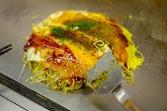 Okonomiyaki, Hiroshima-style, includes a thin crêpe-like outer layer, tons of cabbage, noodles, various seafoods, and numerous sauces.
